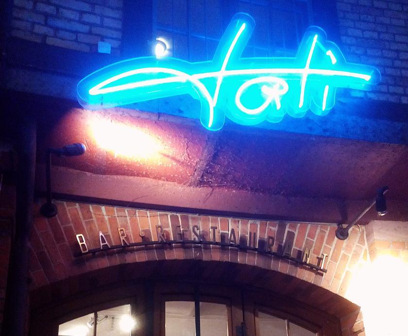 "Leuchtendes Logo des Restaurants ""Tati"" über dem Eingang"