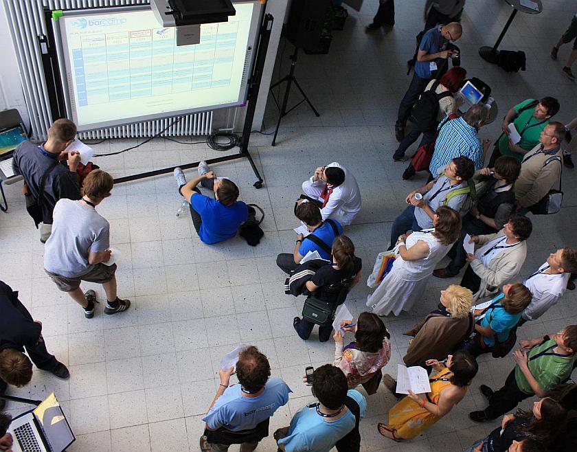 Eine Menge Menschen schaut auf eine Leinwand mit dem Sessionplan, von oben