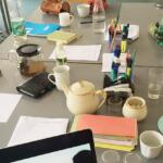 Ein Tisch mit vielen Dingen wie Notizzettel, Laptop, Kaffee und Teetassen,...