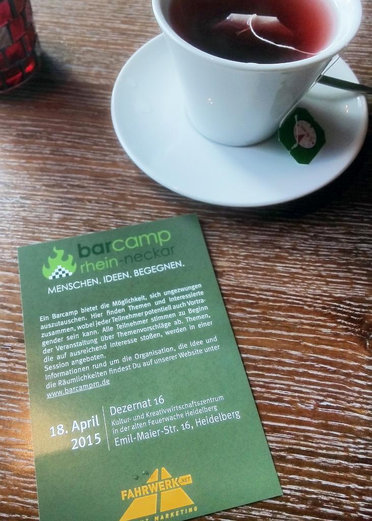 Ein Barcamp Flyer liegt auf einem Holztisch mit einer Tasse Tee