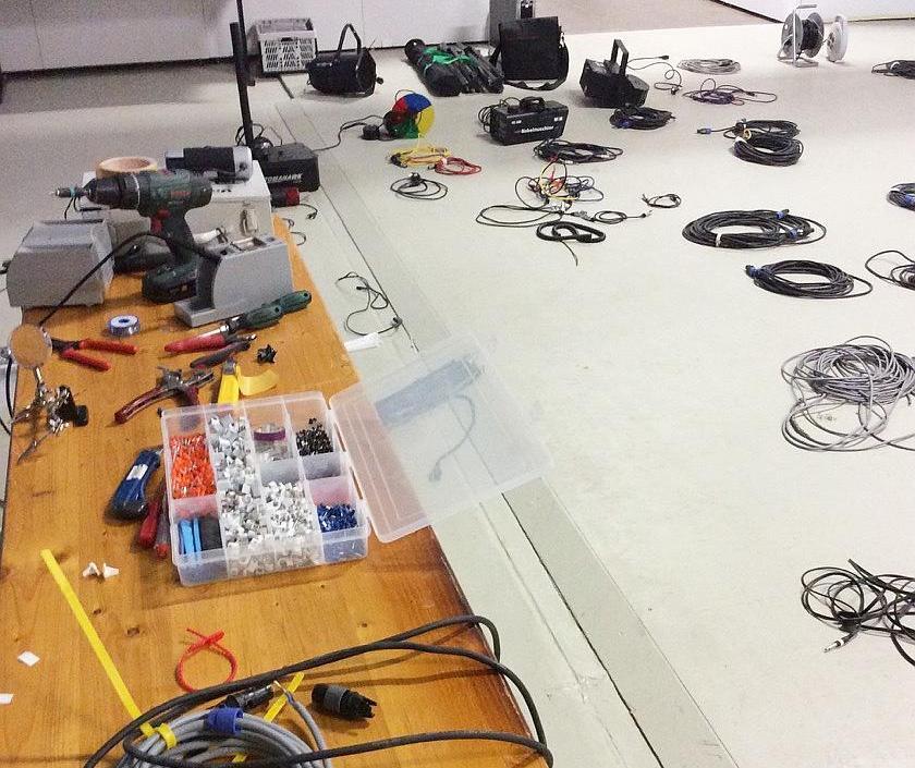 Du siehst einen Tisch mit Werkzeug, dahinter liegen Kabel zusammengerollt auf dem Boden.