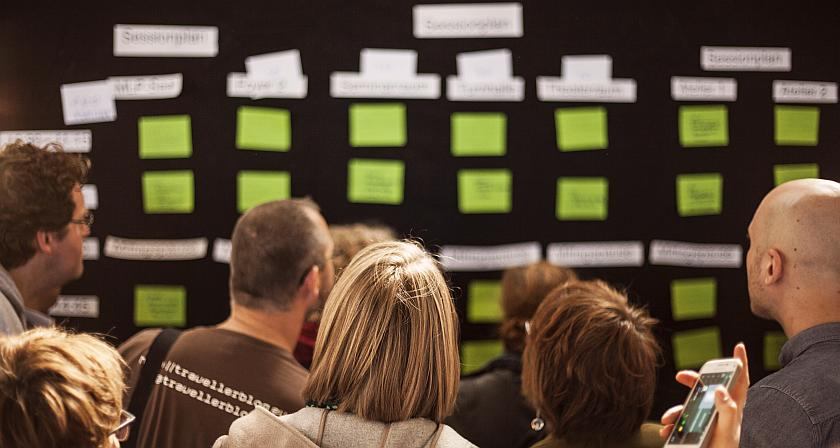 Menschen schauen auf die Wand mit dem Sessionplan