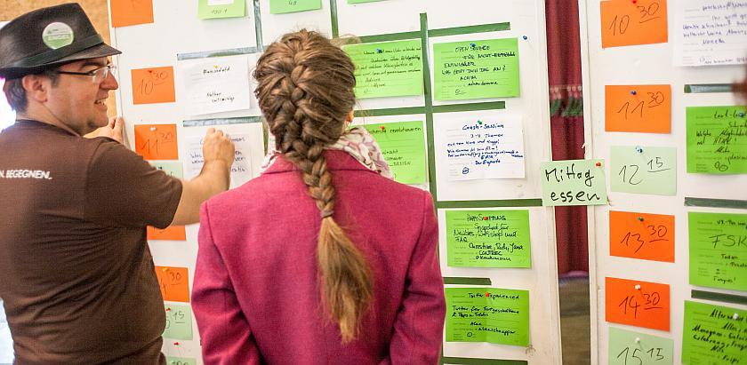 Zwei Personen stehen vor einer Wand, die mit Zetteln gespickt ist. Auf diesen stehen die Sessionvorschläge.