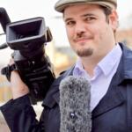 Adrian trägt eine helle Kappe und einen blauen Sommermantel. In der rechten Hand hält er eine kleine Fernsehkamera, in der linken Hand ein Mikrofon mit Windschutz