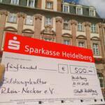 Ein üpbergroßer Scheck vor dem Heidelberger Rathaus.