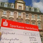 Ein üpbergroßer Scheck vor dem Heidelberger Rathaus. Zuschnitt