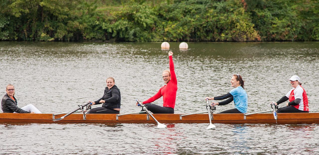 Ein Team im Ruderboot freut sich nach dem erfolgreichen Lauf.