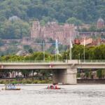 Mehrere Ruderboote vor einer Brücke. Im Hintergrund das Heidelberger Schloss.