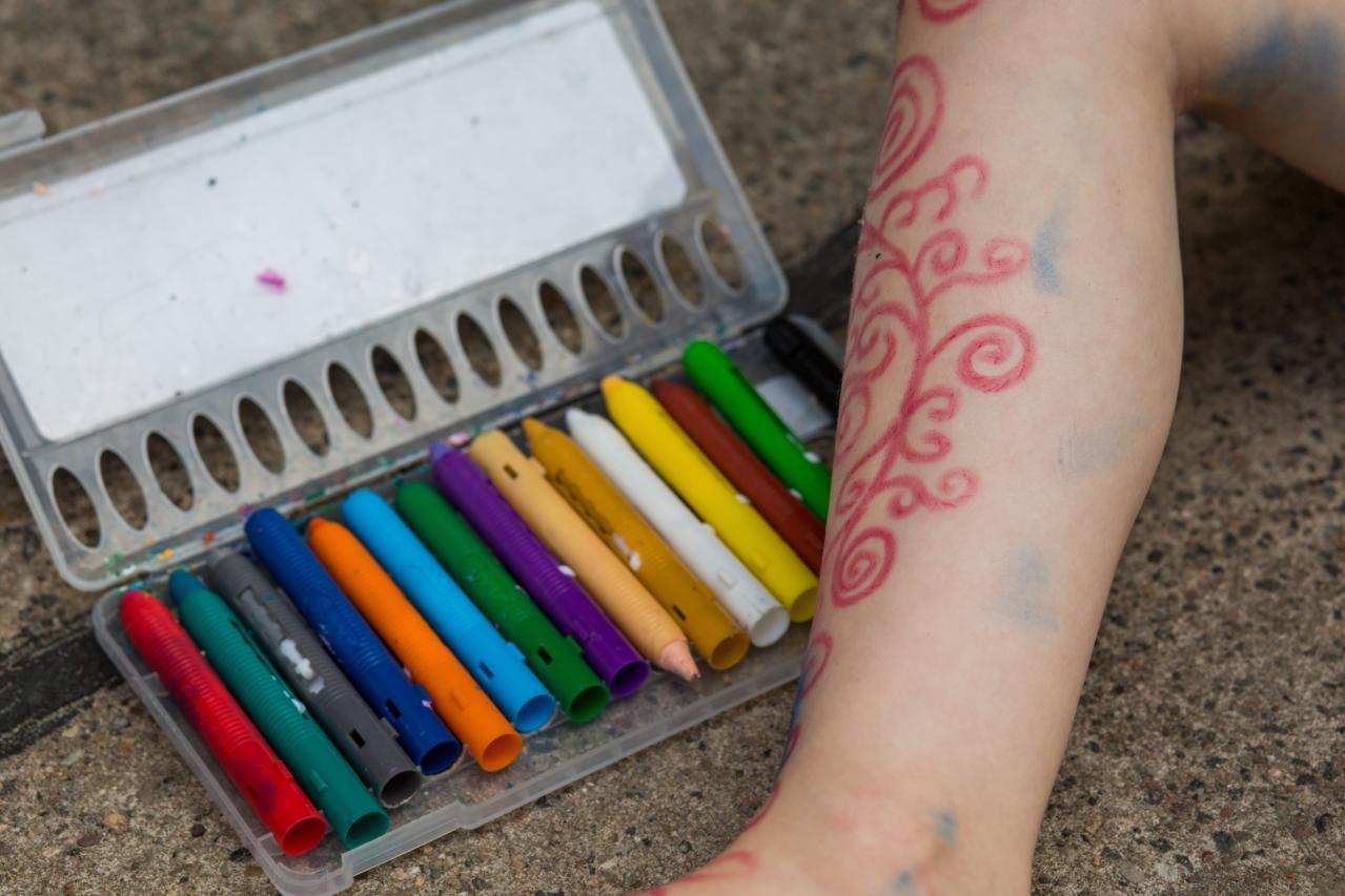 verschiedenfarbige Malfarben und ein künstlerisch bemaltes Kinderbein.