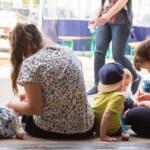 Kinderbetreuung und einige Kinder sitzen im Hof