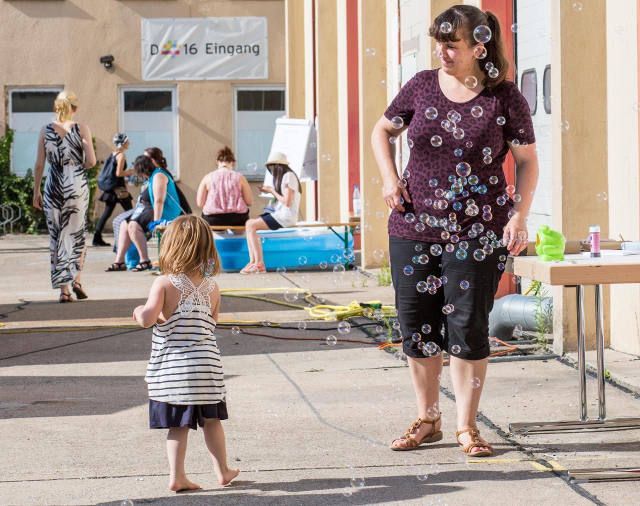 Ein Kind freut sich an einer Fülle an Seifenblasen aus der Maschine.