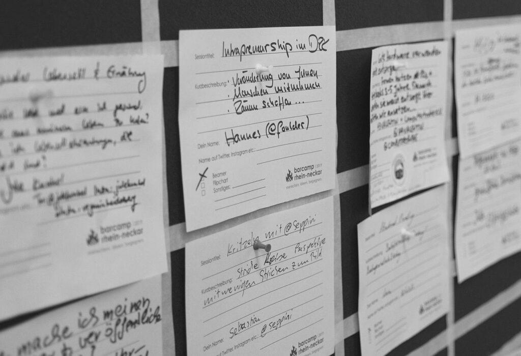 Mehrere Programmpunkte als Sessionkarte an eine Wand gepinnt.