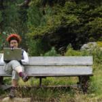 Eine Person sitzt in der Natur mit einem Notebook auf dem Schoß darauf ist eine Kamera angebracht